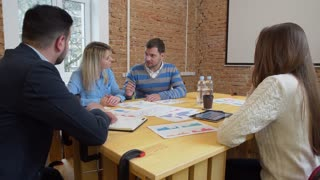 Creative Business team meeting man manager presenting financial data to shareholders using digital tablet in casual modern office boardroom with natural light