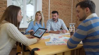 Creative Business team meeting woman manager presenting financial data to shareholders using digital tablet in casual modern office boardroom with natural light