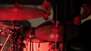 Drummer man plays music on drumsplate at concert stage. Close up drummer with drumstick playing on drum set at rock concert. Man playing rock music on on drum kit at performance