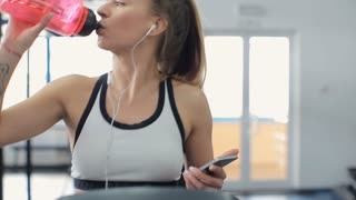 Fit athletic girl is drinking protein shake while exercising on treadmill in sport gym.