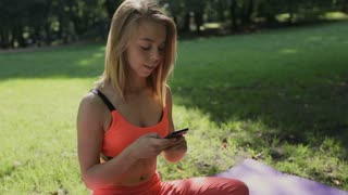 Girl sitting on exercising mat in the park and texting on smartphone