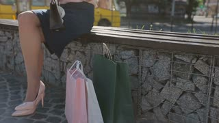 Girl walking in high heels holding shopping bags