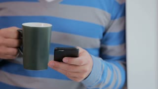 Good looking man drinking coffee using smartphone at the loft modern office. Close-up