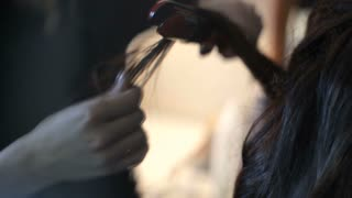Hairdresser makes hairstyle for the bride