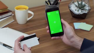 Hands holding credit card and using mobile smart phone Online shopping.Chroma Key. Close up. Tracking motion.