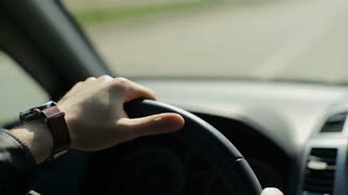 Hands of a man driving a car