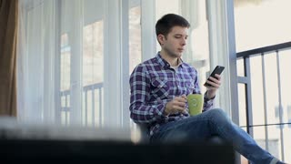 Handsome man at home drinking coffee using smartphone loft apartment