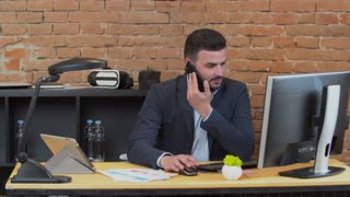 Handsome man city takes a phone call at his desk in a busy office