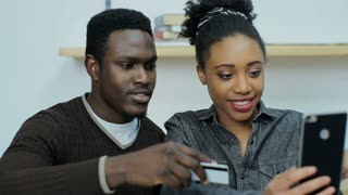 Happy african couple shopping online with credit card using digital tablet woman excited for vacation being booked