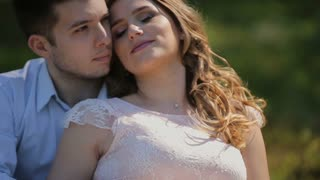 Happy pregnant woman and her husband in the forest. Happy couple waiting for a child.Man caressing woman's belly and hugging woman