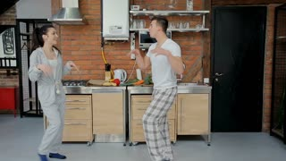 Happy young couple dancing listening to music in kitchen wearing pajamas coffee morning at home having fun