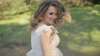 Happy young pregnant woman in a beautiful dress smiling. A woman waiting for a child. The concept of tenderness pregnancy and motherhood.