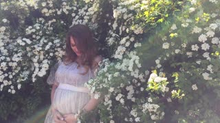 Happy young pregnant woman in a beautiful dress smiling in a park. A woman waiting for a child. The concept of tenderness pregnancy and motherhood.