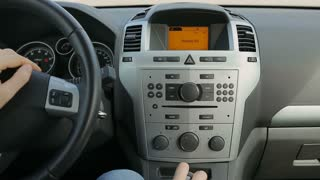 Human driving car and pushing buttons on radio, dashboard