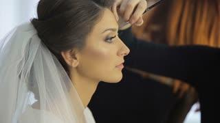 Make up artist putting on mascara on model's eyes. Eye make up
