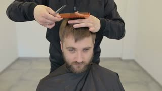 Making haircut look perfect. Young bearded man getting haircut by hairdresser while sitting in chair at barbershop, hairdresser styling.