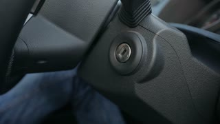 Male hand starting a car engine with ignition key close up shot
