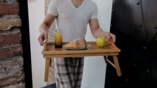 Man bringing wife breakfast in bed on tray carry through house to bedroom surprising happy woman