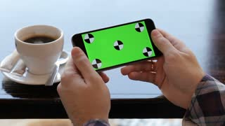 Man hold mobile cell phone with green touch screen in cafe. landscape view