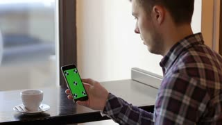 Man hold mobile cell phone with green touch screen in cafe