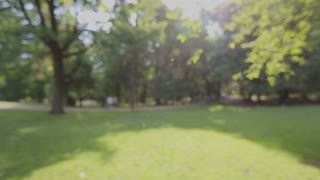 Man holding black smartphone with green screen on park background. Outdoors in park. Chroma key. Close up.
