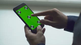 Man Holding Smartphone Touch Screen With Green Screen Chroma Key For Custom Content