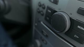 Man increases the volume of the music in the car. Male hand. Close up.