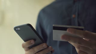 Man inserting credit card number on mobile phone, Online banking with smart phone