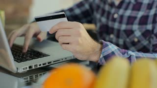 Man online banking using laptop computer shopping online with credit card at home lifestyle