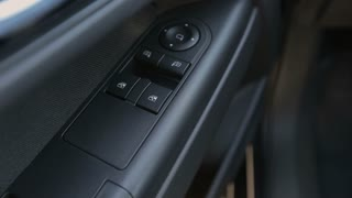 Man opens windows in modern car - detail of control buttons panel
