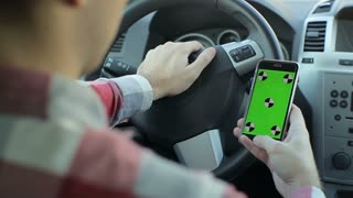 Man sits in the modern car and works on smartphone - green screen, chroma key - closeup. Green screen.Chroma key