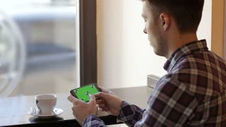 Man texting on smartphone and drinking coffee in cafe. landscape view