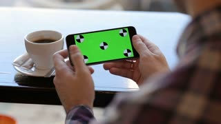Man using app on mobile cell phone with green touch screen in cafe. landscape view