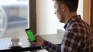 Man using app on mobile cell phone with green touch screen in cafe
