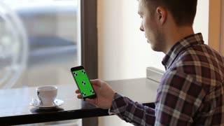 Man using mobile cell phone with green touch screen in cafe