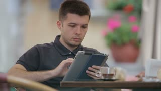 Man using Tablet  and Drinking Coffee in Cafe.
