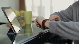 Man using tablet computer and smart watch in the office, close up