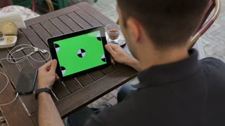 Man using Tablet in Coffee Shop. Tablet with Green Screen