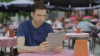 Man using Tablet in Coffee Shop.