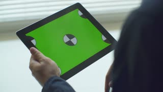 Man using Tablet.Tablet with Green Screen