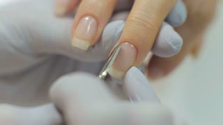 Manicure. Closeup Of Manicurist Hands Removing Cuticle From Female Nails With Professional Metal Nail Scissors. Woman Hand With Healthy Natural Nails Getting Nails Care Procedure. High Resolution