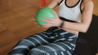 Muscular woman exercising with a weight ball. Fitness woman working out on core muscles at cross fit gym. Weight ball torso twist on exercise mat.