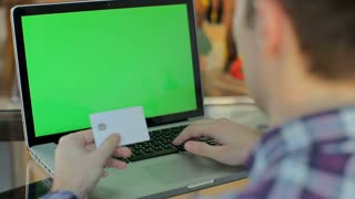 Online shopping. Male hand holding a gold credit card and shopping online. Green screen, chroma key