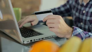 Online shopping. Male hand holding a gold credit card and shopping online.