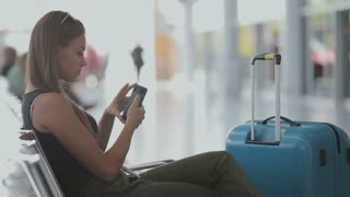 Pretty young female passenger using phone at the airport