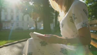 Romantic girl reading a book in the park in sunrise