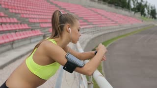 Runner stops to take a break and enjoy music and exercising outdoors with fitness tracker