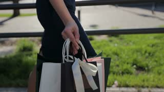 Sale, consumerism: Confident lady with shopping bags walking in a city