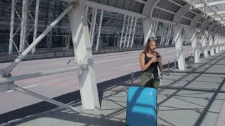Sexy fit attractive young business woman with luggage at the airport waiting for a bus