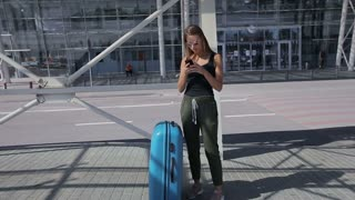 Sexy fit attractive young business woman with luggage at the airport waiting for a taxi